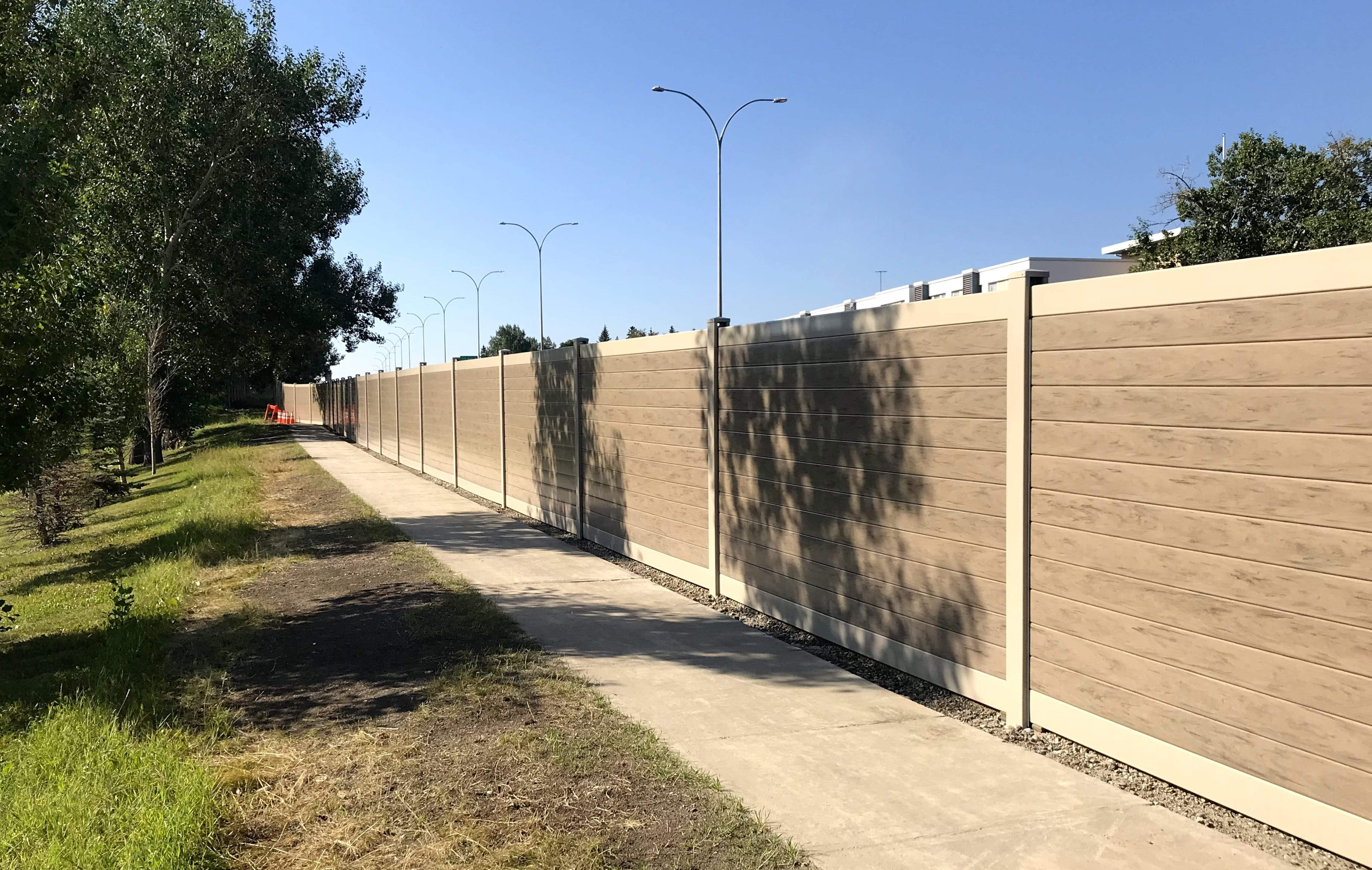 Closer sidewalk view of Calgary highway sound barrier wall